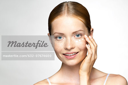 Young woman applying undereye cream Stock Photo - Premium Royalty-Free, Image code: 632-07674600