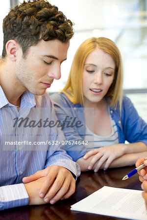 Clients reviewing contract with advisor Stock Photo - Premium Royalty-Free, Image code: 632-07674642
