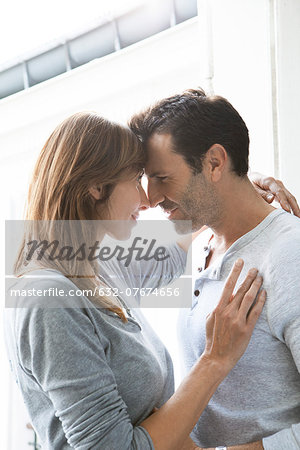 Couple touching noses and embracing by open window Stock Photo - Premium Royalty-Free, Image code: 632-07674656