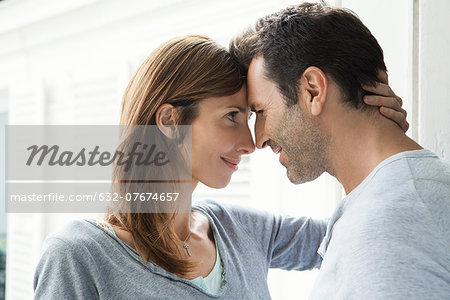 Couple touching noses by window Stock Photo - Premium Royalty-Free, Image code: 632-07674657