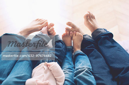Outstretched legs and barefeet of family with two children Stock Photo - Premium Royalty-Free, Image code: 632-07674682