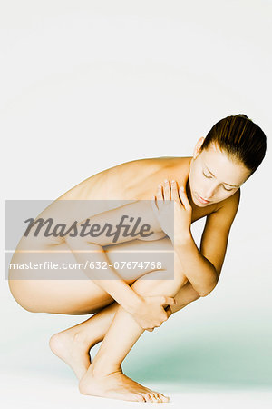 Nude woman crouching, side view Stock Photo - Premium Royalty-Free, Image code: 632-07674768