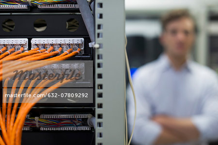 Network cables connected to computer mainframe, computer technician in background Stock Photo - Premium Royalty-Free, Image code: 632-07809292
