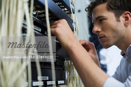 Computer technician performing maintenance on computer networking equipment Stock Photo - Premium Royalty-Free, Image code: 632-07809331