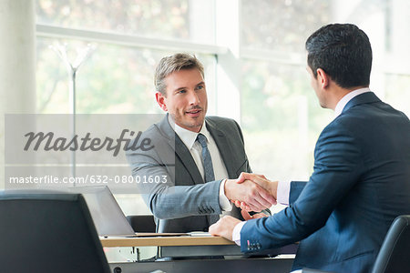 Businessmen shaking hands in meeting Stock Photo - Premium Royalty-Free, Image code: 632-08001603