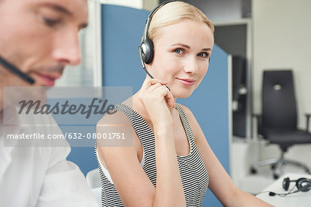 Woman wearing phone headset at desk Stock Photo - Premium Royalty-Free, Image code: 632-08001751