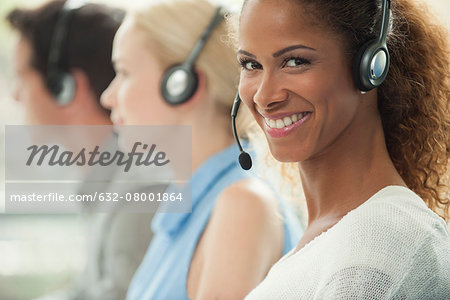 Woman working in call center, smiling cheerfully Stock Photo - Premium Royalty-Free, Image code: 632-08001864