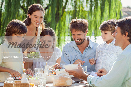 Family enjoying breakfast together outdoors Stock Photo - Premium Royalty-Free, Image code: 632-08129730