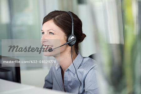 Receptionist wearing headset, smiling cheerfully Stock Photo - Premium Royalty-Free, Image code: 632-08129778