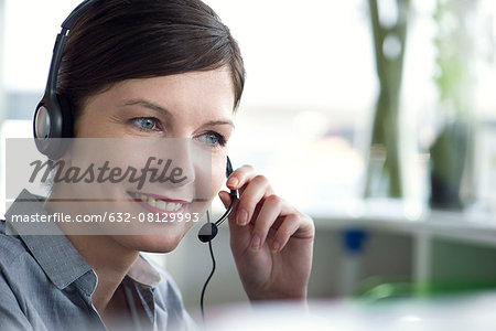 Receptionist using telephone headset Stock Photo - Premium Royalty-Free, Image code: 632-08129993