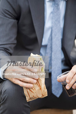 Businessman holding sandwich, cropped Stock Photo - Premium Royalty-Free, Image code: 632-08227482
