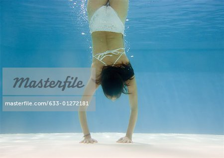 Teenage girl doing handstand underwater