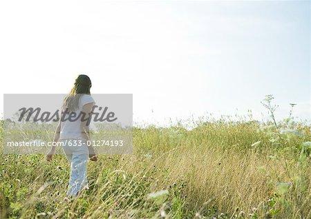 Girl walking through tall grass in field