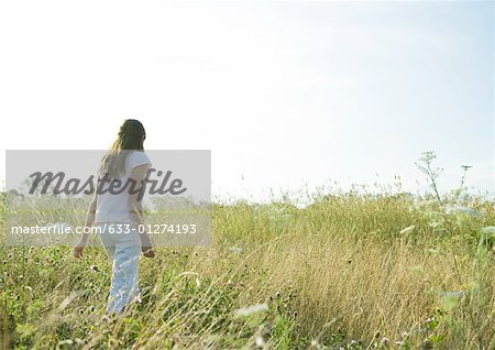 Girl walking through tall grass in field