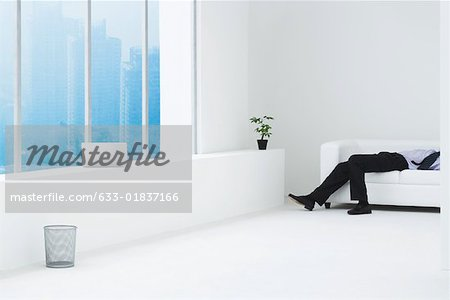 Businessman lying on sofa in minimalist high rise apartment, cropped view Stock Photo - Premium Royalty-Free, Image code: 633-01837166