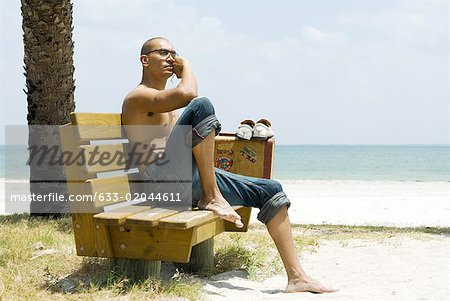 Man at the beach, sitting on bench beside suitcase, looking away Stock Photo - Premium Royalty-Free, Image code: 633-02044611