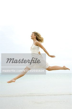 Woman jumping in the air at the beach, side view Stock Photo - Premium Royalty-Free, Image code: 633-02065824