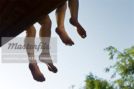 Adult and child sitting on deck with legs dangling off edge, cropped Stock Photo - Premium Royalty-Free, Image code: 633-03444465