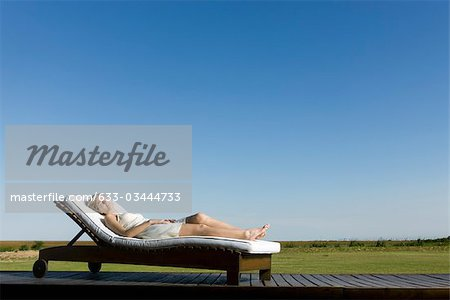 Woman napping on lounge chair on deck Stock Photo - Premium Royalty-Free, Image code: 633-03444733