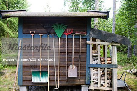 Gardening tools hung on side of shed Stock Photo - Premium Royalty-Free, Image code: 633-03444801