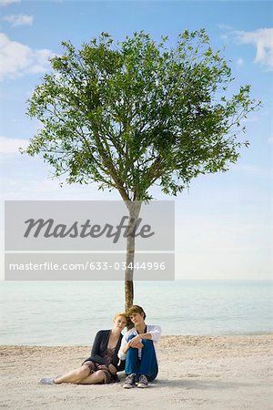 Young couple sitting together beneath tree on beach Stock Photo - Premium Royalty-Free, Image code: 633-03444996