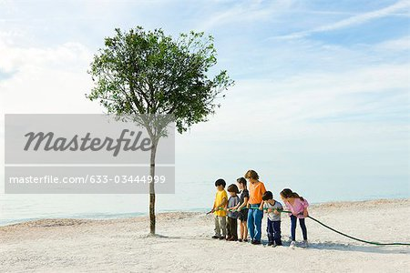 Ecology conceZS, children watering tree growing on beach Stock Photo - Premium Royalty-Free, Image code: 633-03444999