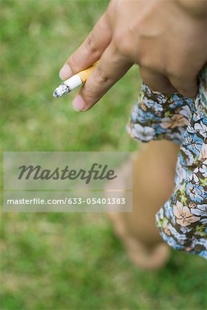 Woman's hand holding cigarette, cropped Stock Photo - Premium Royalty-Free, Image code: 633-05401383