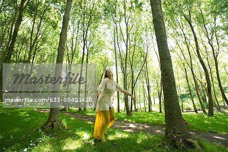 Young woman standing on one leg in woods Stock Photo - Premium Royalty-Free, Image code: 633-05401428