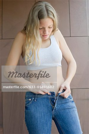 Young woman buttoning tight jeans Stock Photo - Premium Royalty-Free, Image code: 633-05401602