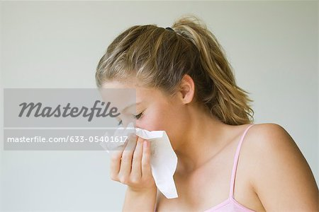 Young woman sneezing into tissue Stock Photo - Premium Royalty-Free, Image code: 633-05401617