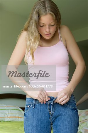 Young woman buttoning tight jeans Stock Photo - Premium Royalty-Free, Image code: 633-05401778