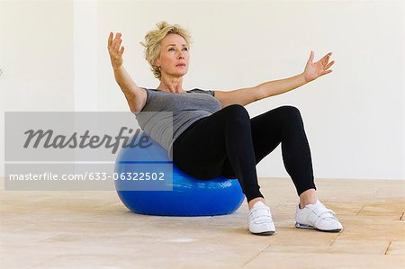 Mature woman doing pilates exercise on fitness ball Stock Photo - Premium Royalty-Free, Image code: 633-06322502