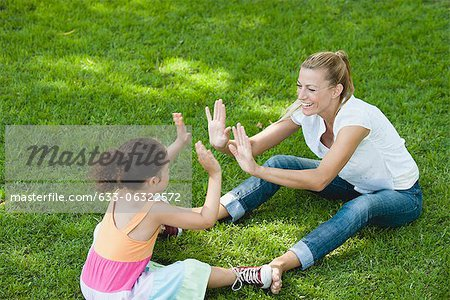 Mother and daughter sitting on grass playing patty-cake Stock Photo - Premium Royalty-Free, Image code: 633-06322572