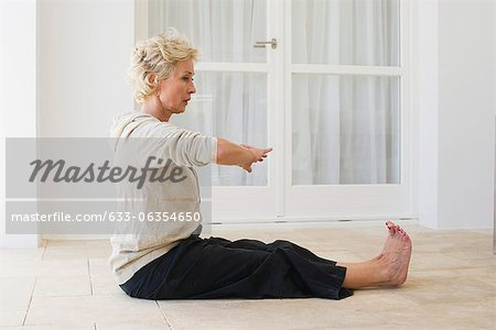 Mature woman practicing yoga on floor Stock Photo - Premium Royalty-Free, Image code: 633-06354650