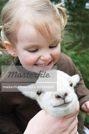 Little girl petting lamb Stock Photo - Premium Royalty-Free, Image code: 633-06354688