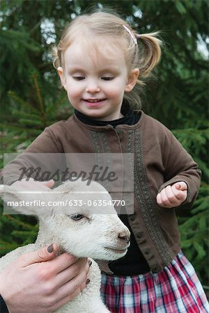 Little girl petting lamb Stock Photo - Premium Royalty-Free, Image code: 633-06354770