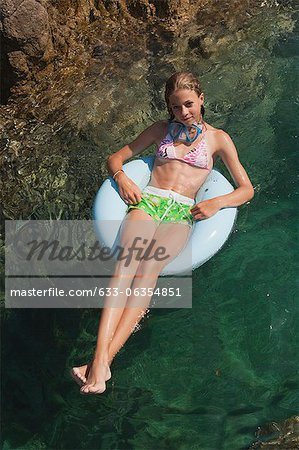 Preteen girl floating on water Stock Photo - Premium Royalty-Free, Image code: 633-06354851