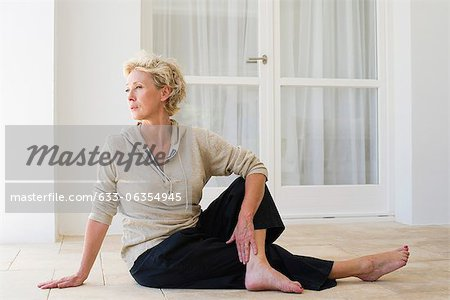 Mature woman sitting on floor doing spinal twist Stock Photo - Premium Royalty-Free, Image code: 633-06354945