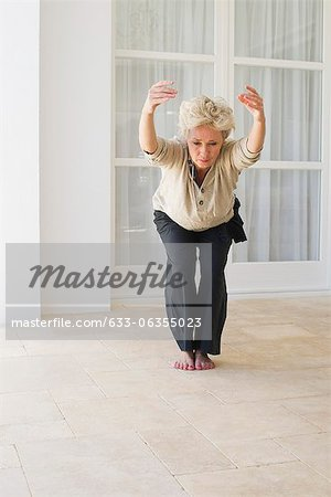 Mature woman doing yoga chair pose Stock Photo - Premium Royalty-Free, Image code: 633-06355023