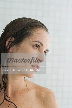 Woman in shower, looking away in thought Stock Photo - Premium Royalty-Free, Image code: 633-06355035