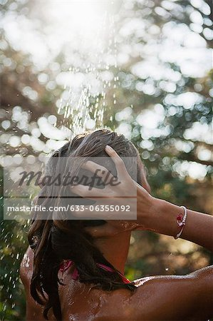 Girl washing hair under running water outdoors, rear view Stock Photo - Premium Royalty-Free, Image code: 633-06355092