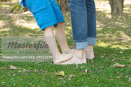 Little boy standing barefoot on father's feet, cropped Stock Photo - Premium Royalty-Free, Image code: 633-08151098