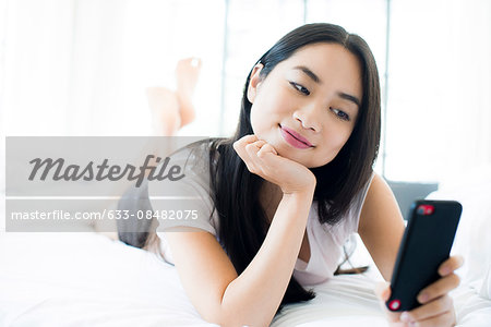 Woman lying on bed, smiling at smartphone Stock Photo - Premium Royalty-Free, Image code: 633-08482075