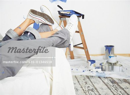 Man and woman waist down on sofa with paint Stock Photo - Premium Royalty-Free, Image code: 635-01346518