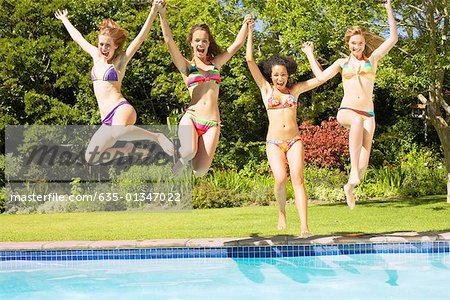 Four teenage girls jumping into pool Stock Photo - Premium Royalty-Free, Image code: 635-01347022