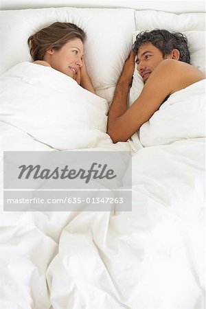 Woman and man lying down in bed Stock Photo - Premium Royalty-Free, Image code: 635-01347263