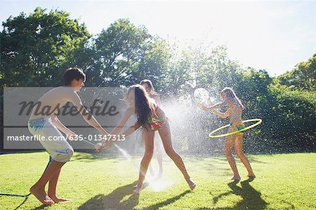 Teenage boy spraying teenage girls with hose outdoors Stock Photo - Premium Royalty-Free, Image code: 635-01347313