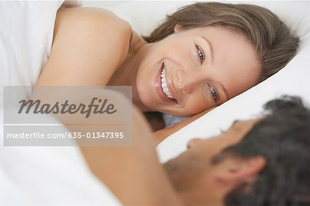 Woman and man lying down in bed Stock Photo - Premium Royalty-Free, Image code: 635-01347395