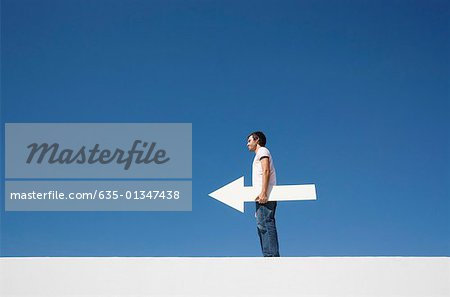 Man outdoors on wall with blank arrow Stock Photo - Premium Royalty-Free, Image code: 635-01347438