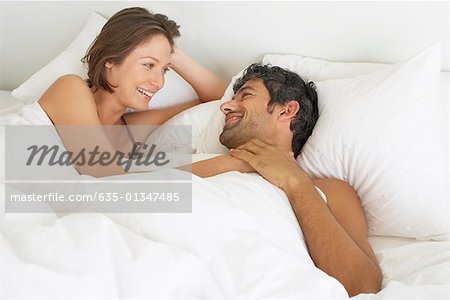 Woman and man lying down in bed Stock Photo - Premium Royalty-Free, Image code: 635-01347485